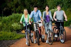 Jeunes adultes sur des vélos Image libre de droits