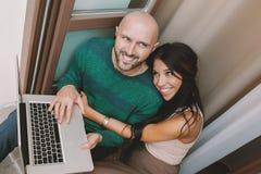 Jeunes ajouter à l'ordinateur portable au balcon Image stock
