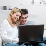 Jeunes ajouter à l'ordinateur portatif à la maison photos stock