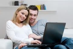 Jeunes ajouter à l'ordinateur portatif à la maison Photographie stock libre de droits