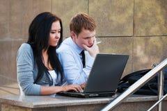 Jeunes ajouter à l'ordinateur portatif. photographie stock libre de droits