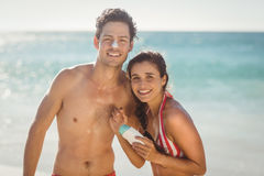 Jeunes ajouter à la lotion de protection solaire sur la plage Photo stock