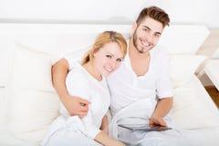 Jeunes ajouter à une tablette dans le lit Image stock