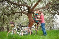 Jeunes ajouter affectueux au jardin de bicyclettes au printemps Photo stock