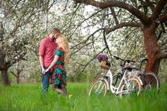 Jeunes ajouter affectueux au jardin de bicyclettes au printemps Images libres de droits