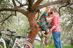 Jeunes ajouter affectueux au jardin de bicyclettes au printemps Photos libres de droits