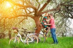 Jeunes ajouter affectueux au jardin de bicyclettes au printemps Photographie stock