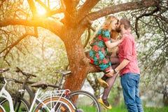 Jeunes ajouter affectueux au jardin de bicyclettes au printemps Image stock