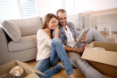 Jeunes ajouter au comprimé à leur nouvel appartement photographie stock libre de droits