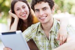 Jeunes ajouter au comprimé numérique Image stock