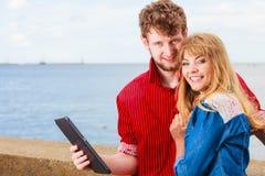 Jeunes ajouter au comprimé par le bord de la mer extérieur Photo stock
