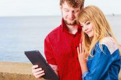 Jeunes ajouter au comprimé par le bord de la mer extérieur Photo libre de droits