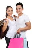 Jeunes ajouter au sac à provisions Photographie stock