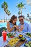 Jeunes ajouter au smartphone dans le restaurant de piscine Images stock