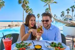 Jeunes ajouter au smartphone dans le restaurant de piscine Photographie stock