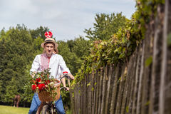 Jeunes ajouter au tandem de vélo en parc La fille tient une sucrerie sous forme de coeur Photographie stock libre de droits