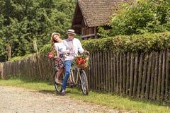 Jeunes ajouter au tandem de vélo en parc La fille tient une sucrerie sous forme de coeur Photographie stock