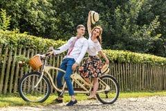Jeunes ajouter au tandem de vélo en parc Les jeunes maintiennent des chapeaux dans leurs mains et sourire Au dos de la barrière d Images stock