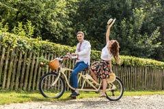 Jeunes ajouter au tandem de vélo en parc Les jeunes maintiennent des chapeaux dans leurs mains et sourire Au dos de la barrière d Photos libres de droits