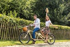 Jeunes ajouter au tandem de vélo en parc Les jeunes maintiennent des chapeaux dans leurs mains et sourire Au dos de la barrière d Photo stock