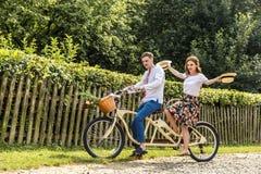 Jeunes ajouter au tandem de vélo en parc Les jeunes maintiennent des chapeaux dans leurs mains et sourire Au dos de la barrière d Image stock