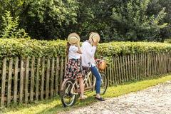 Jeunes ajouter au tandem de vélo en parc Les jeunes tiennent leurs chapeaux dans leurs mains, fermant leurs visages Photographie stock