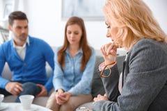Jeunes ajouter au thérapeute de thérapie familiale de psychologue regardant en bas de réfléchi image libre de droits