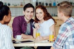 Jeunes ajouter aux amis en café Images stock