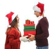 Jeunes ajouter aux cadeaux de Noël sur le fond blanc photo stock
