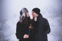 Jeunes ajouter aux cierges magiques dans la famille de sourire de forêt d'hiver avec des lumières de Bengale Photographie stock libre de droits
