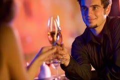 Jeunes ajouter aux glaces de champagne dans le restaurant Photographie stock libre de droits
