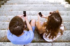 Jeunes ajouter aux smartphones se reposant sur des escaliers Photos stock