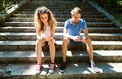 Jeunes ajouter aux smartphones se reposant sur des escaliers en ville Images libres de droits