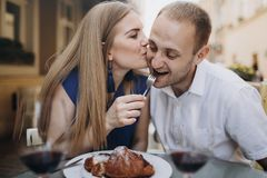Jeunes ajouter aux verres de vin rouge dans un restaurant image libre de droits