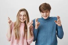 Jeunes ajouter caucasiens aux yeux fermés, au froncement de sourcils leurs visages et aux doigts de croisement souhaitant quelque Photos stock