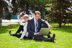 Jeunes ajouter d'affaires à l'ordinateur portatif Photo stock