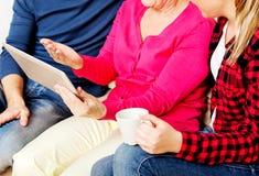 Jeunes ajouter à dame âgée s'asseyant sur le divan et observant quelque chose sur le comprimé Photographie stock