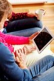 Jeunes ajouter à dame âgée s'asseyant sur le divan et observant quelque chose sur le comprimé Image stock