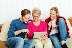 Jeunes ajouter à dame âgée s'asseyant sur le divan et observant quelque chose sur le comprimé Photo stock
