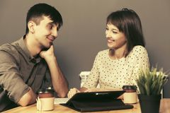 Jeunes ajouter heureux à la tablette numérique se reposant à la table Photographie stock