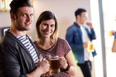 Jeunes ajouter heureux à la tasse de bière Image libre de droits