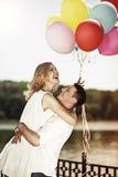 Jeunes ajouter heureux attrayants à l'embrassement coloré de ballons Images stock