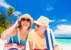 Jeunes ajouter heureux aux accessoires de plage ayant l'amusement par la plage Image stock