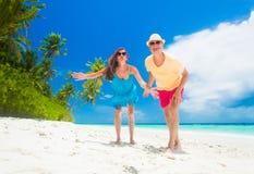 Jeunes ajouter heureux aux accessoires de plage ayant l'amusement par la plage Image libre de droits