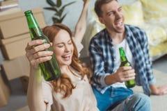 jeunes ajouter heureux aux bouteilles de bière au nouvel appartement, photo libre de droits