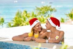 Jeunes ajouter heureux aux chapeaux de Santa appréciant dans la piscine Photographie stock libre de droits