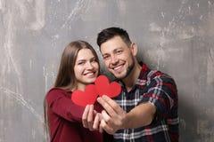 Jeunes ajouter heureux aux coeurs rouges Photographie stock libre de droits