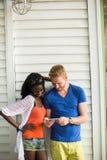 Jeunes ajouter multiraciaux au téléphone portable Image stock