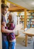 Jeunes ajouter romantiques à l'étagère à la distance dans la bibliothèque Photo libre de droits