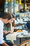 Jeunes ajouter romantiques à la carte en café français Image stock